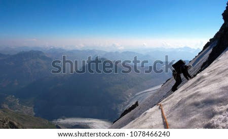 mountain climber traverses a blank ice field on a high alpine peak with a great view behind #1078466240