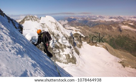 mountain climber traversing a very steep glacier with a great mountain landscape view behind him near St. Moritz #1078464938