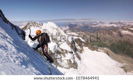 mountain climber traversing a very steep glacier with a great mountain landscape view behind him near St. Moritz #1078464941