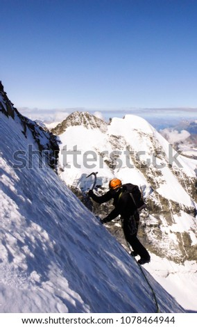 mountain climber traversing a very steep glacier with a great mountain landscape view behind him near St. Moritz #1078464944