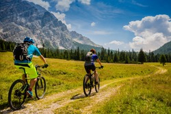 Mountain cycling couple with bikes on track, Cortina d'Ampezzo, Dolomites, Italy