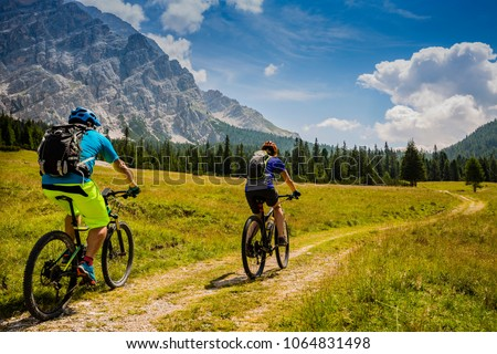 Mountain cycling couple with bikes on track, Cortina d'Ampezzo, Dolomites, Italy #1064831498