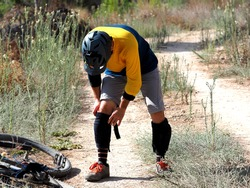 Mountain cyclist puts bicycle knee pads to protect his knees during enduro ride.