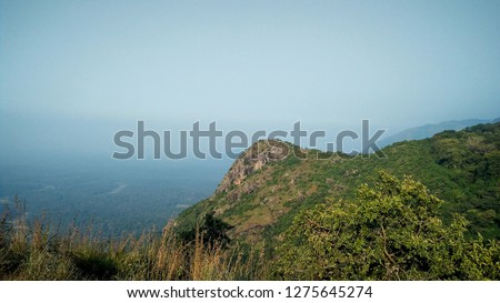 Mountain edge surrounded by green trees under blue sky in ooty India #1275645274