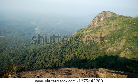 Mountain edge surrounded by green trees under blue sky in ooty India #1275645280