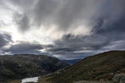 Mountain epic clouds view autumn Norway landscape travel Tindevegen. Dramatic sky cloudscape and blue hills