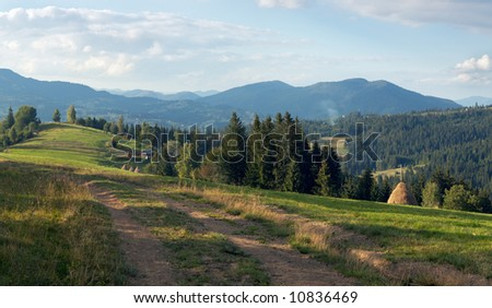 Mountain evening view with earth road, haystacks and country estate (Slavske village outskirts, Carpathian Mt's, Ukraine). Four shots composite picture.