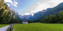 Mountain farm house on meadow in European Alps, located in Robanov kot, Slovenia, popular hiking and climbing place with picturescue view