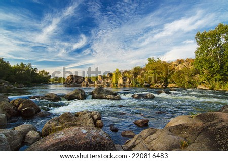 Mountain fast flowing river stream of water in the rocks with blue sky