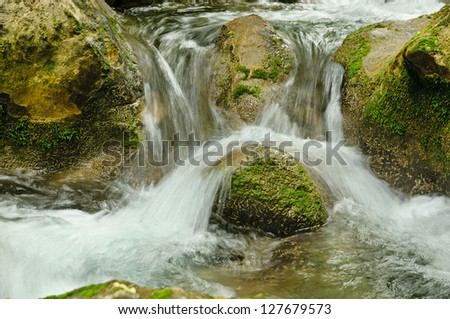 mountain fast flowing river stream of water in the rocks with moss
