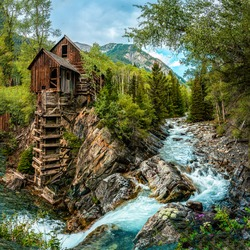 Mountain forest river hut waterfall. Forest hut on mountain river. Mountain cabin at river waterfall. Forest hut in mountains