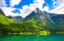 Mountain green lake landscape. Green lake in mountains. Mountain lake view. Mountain lake village