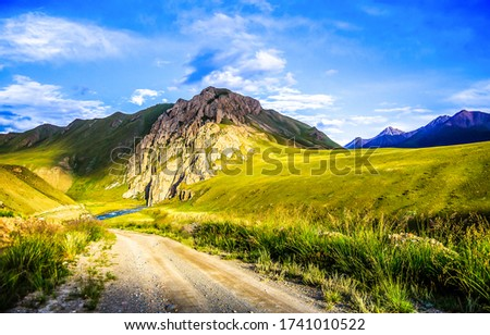 Mountain green valley road landscape. Green hill valley road view. Road in mountain hill valley