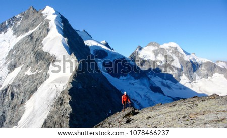 mountain guide arrives at the summit of a high alpine peak with the beautiful and famous snow shite Bianco Ridge behind him #1078466237
