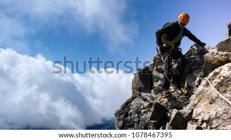 mountain guide on a rocky ridge under a blue sky close up on his way to the summit with a client #1078467395