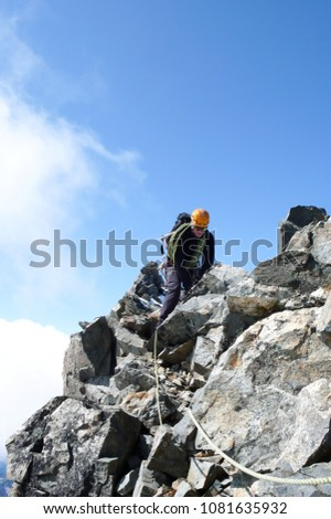 mountain guide on a steep and exposed rocky ridge on his way to a high alpine summit with a client #1081635932
