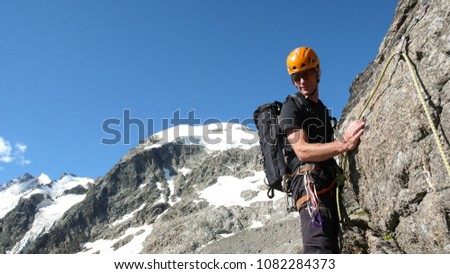mountain guide on a steep and exposed rocky ridge on his way to a high alpine summit with a client #1082284373