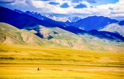 Mountain hill valley landscape. Lone rider in mountain valley. Lone rider in mountains