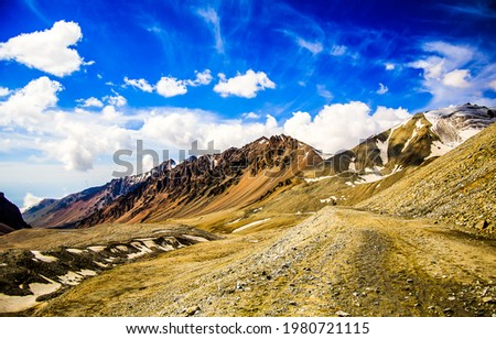 Mountain hills under a clear blue sky. Mountain blue sky with white clouds. Mountain sky landscape