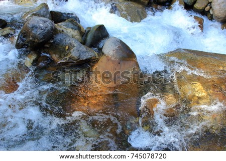 Mountain himalayan waterfall close up with impetuous water flow and water foam and stones. #745078720