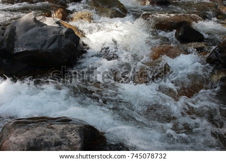 Mountain himalayan waterfall close up with impetuous water flow and water foam and stones. #745078732
