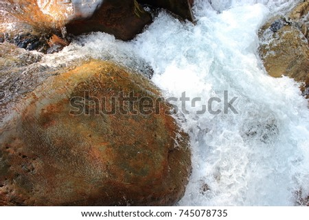 Mountain himalayan waterfall close up with impetuous water flow and water foam and stones. #745078735
