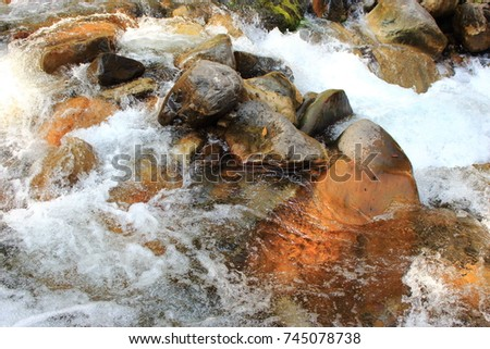 Mountain himalayan waterfall close up with impetuous water flow and water foam and stones. #745078738