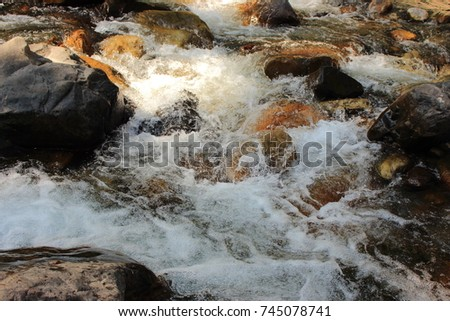 Mountain himalayan waterfall close up with impetuous water flow and water foam and stones. #745078741
