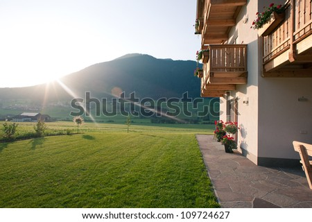 Stock Photo Mountain house at sunset. Dolomites, Italy.