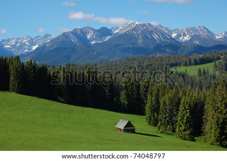 Mountain hut on green field with Tatra peaks in the distance