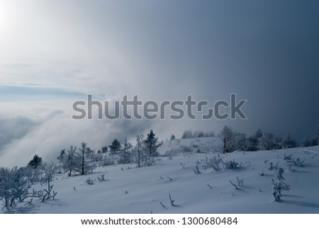 Mountain hut with amazing winter landscape, deep snow, clouds, above the clouds, deep snow, cold weather