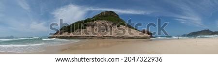Mountain known as 'pedra do Pontal', located on Praia do Pontal in the district of Recreio dos Bandeirantes, Rio de Janeiro, Brazil. Where you can see the mountain, the beach, and the people on the sa Foto stock ©