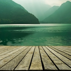 Mountain lake and flowing river with a wooden bridge