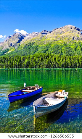 Mountain lake boats view. Lake boats in mountains. Mountain lake boats scene. Mountain lake boats