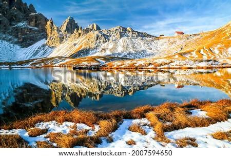Mountain lake in a snowy autumn. Mountain lake view. Lake in mountains. Mountain lake snow