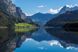 Mountain lake Klontalersee  on background of majestic mountains reflected in the water and bright cloudy sky. Glarus Canton. Swiss Alps. Switzerland. Tourist destination