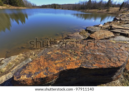 Mountain lake, old rocks and deep blue sky - stock photo
