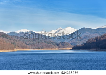 Mountain lake panorama against cloudy sky and mountains covered with snow #534335269