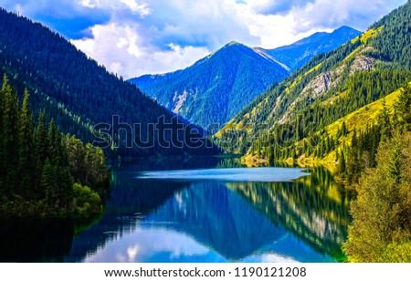 Mountain lake reflection landscape. Mountain forest lake reflection view. Mountain lake water reflection. Mountain forest lake panorama