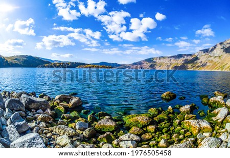 Mountain lake shore on a clear day. Lake in mountains. Mountain lake view. Lake shore in mountains