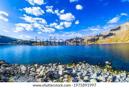 Mountain lake under a blue sky with clouds. Lake view. Lake shore landscape. Mountain lake shore landscape