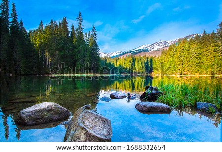 Photo of  Mountain lake water stones landscape. Mountain lake water. Lake in mountains. Mountain lake stones