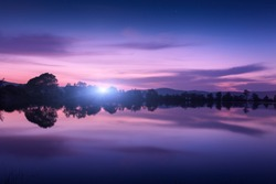 Mountain lake with moonrise at night. Night landscape with river, trees, hills, moon and colorful purple sky with clouds reflected in water in dusk. Beautiful nature background in twilight. Travel