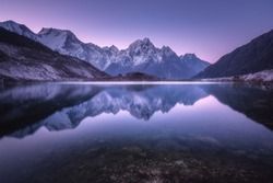 Mountain lake with perfect reflection at sunrise. Beautiful landscape with purple sky, snowy mountains, hills, fog over the lake at twilight in Nepal. Snow covered rocks is reflected in water. Nature