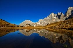 Mountain lake with reflection in Autumn. Alpine landscape at Baita Segantini.