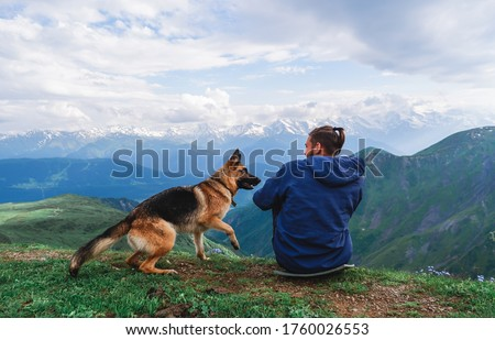Mountain lakes of Koruldi. Caucasian mountains. The peaks of the snowy mountains are reflected in the mountain lake. A man traveler and a dog sit in the mountains, Georgia, Svaneti.  ストックフォト ©
