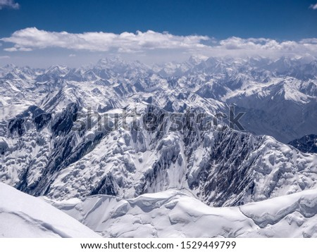 Mountain landscape. Amazing view from the Lenin peak's summit. Snow covered peaks in the Pamir.