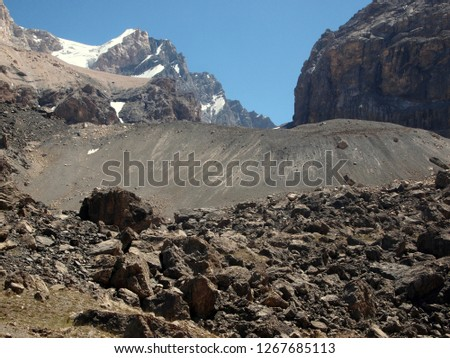 Mountain landscape at high elevation. Taken on the way to Alaudin pass in the Fann mountains (Pamir, Tajikistan) in mid-August. High snowy range in the background, volcanic origin slope and rocks.