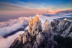 Mountain landscape at sunset. Amazing view from mountain peak on the high rocks, blue sky, clouds and sea in the evening. Low clouds. Colorful nature background. Adventure. Travel in Crimea. Cliffs
