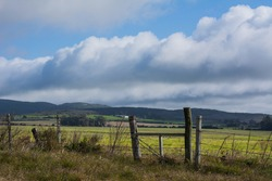 Mountain landscape from the route. Gate of a field or gatekeeper. Natural Uruguay. Clouds and blue sky, nature.